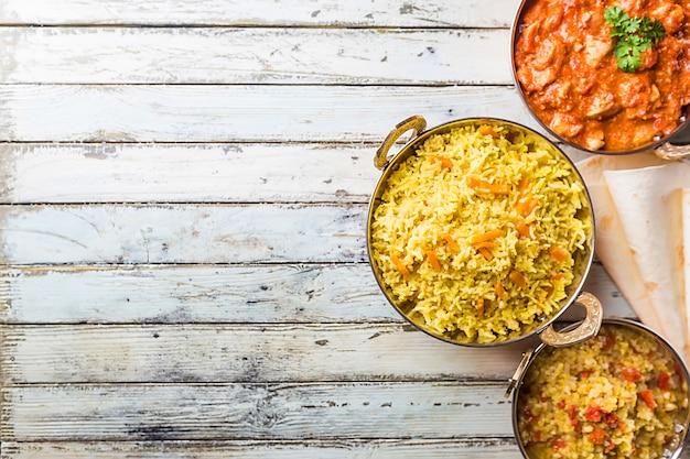 Różne miski z różnymi indyjskimi potrawami na białej powierzchni drewnianej, widok z góry.