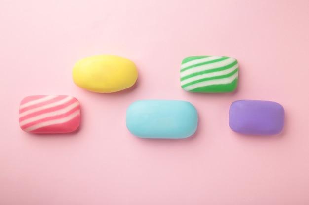 Różne mydła w różnych mydelniczkach. dużo stałego mydła zapewniającego higienę i czystość. kolorowe mydło i resztki są rozrzucone na fioletowym stole.