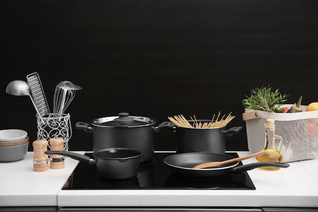 Różne naczynia do gotowania na kuchence elektrycznej na czarnym tle