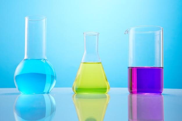 Różne naczynia laboratoryjne z kolorowym płynem na niebieskim tle laboratoryjne badania chemiczne