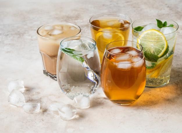 Różne napoje orzeźwiające w szklankach z lodem
