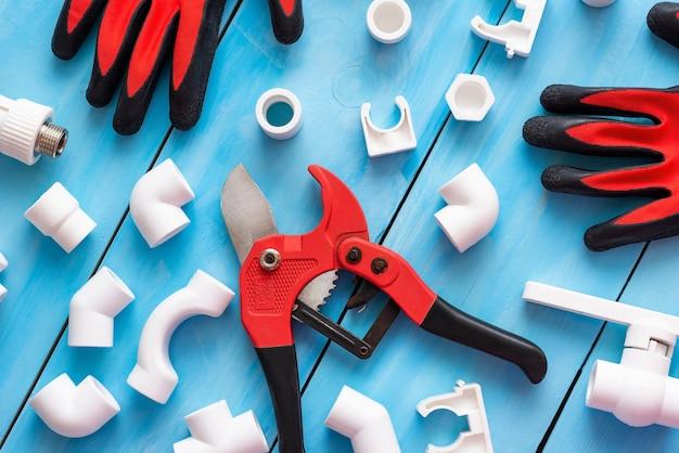 Różne narożniki, adaptery i złączki wraz z rękawicami i obcinakiem do rur z tworzyw sztucznych.