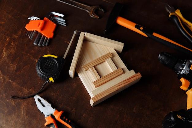 Różne narzędzia do naprawy i model domu zestaw narzędzi do naprawy na tle drewnianych