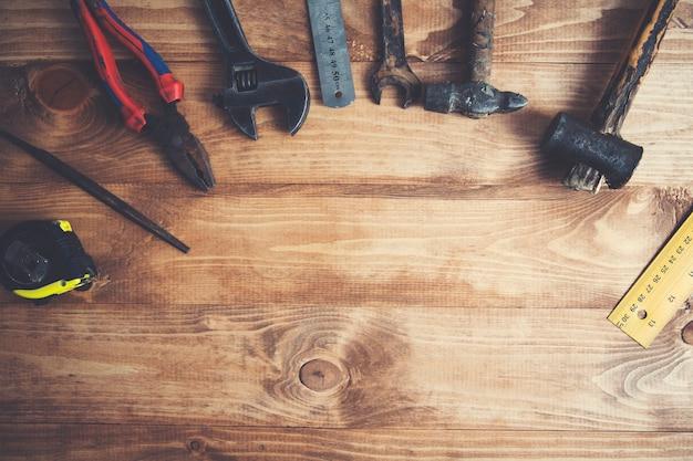 Różne narzędzia na drewnianym stole w tle