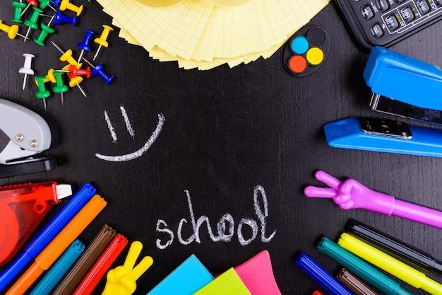 Różne narzędzia szkolne na czarnej tablicy z wiadomością z małym miejscem na kopię w centrum powrót do szkoły