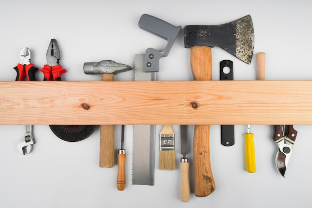 Różne narzędzia wiszące na drewnianej podstawie