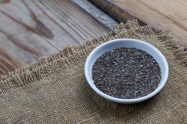 Różne nasiona - sezam, siemię lniane, siemię lniane, nasiona dyni, mak, chia w miskach na rustykalnym. kopiuj .