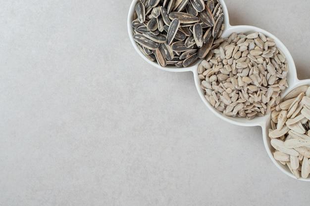 Różne nasiona słonecznika w białych miseczkach