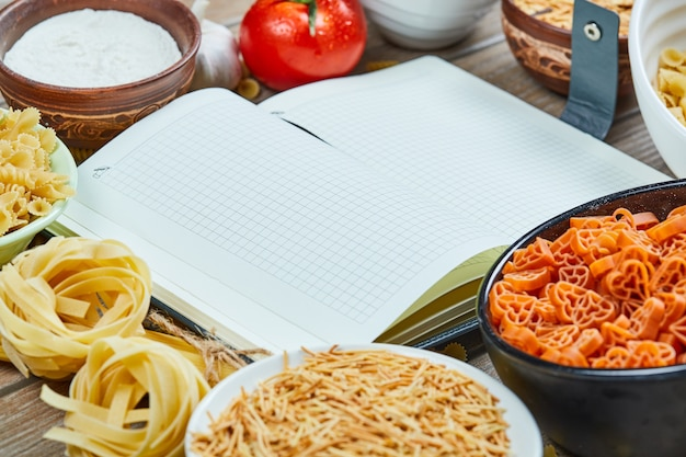 Różne niegotowane makarony z notatnikiem i warzywami na drewnianym stole.