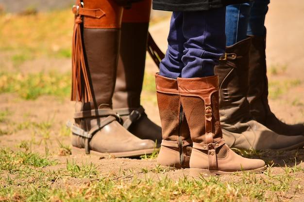 Różne nogi ludzi w butach do jazdy konnej.