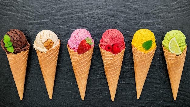 Różne o smaku lodów w rożkach założonych na ciemnym kamiennym tle.