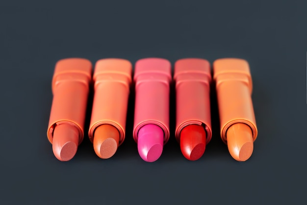 Różne odcienie szminki na tle produktu kosmetycznego