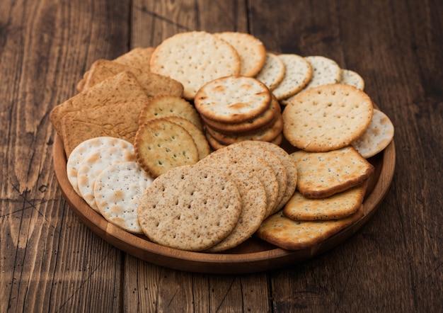 Różne organiczne krakersy chrupiące pszenica, żyto i kukurydza flatbread z sezamem i solą w okrągłym talerzu na tle drewna.