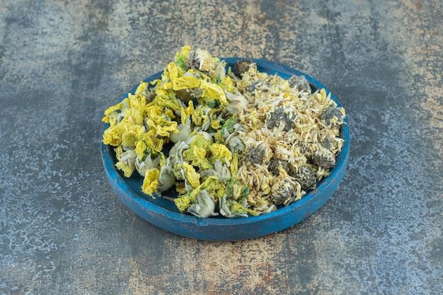 Różne organiczne suche kwiaty na niebieskim talerzu.