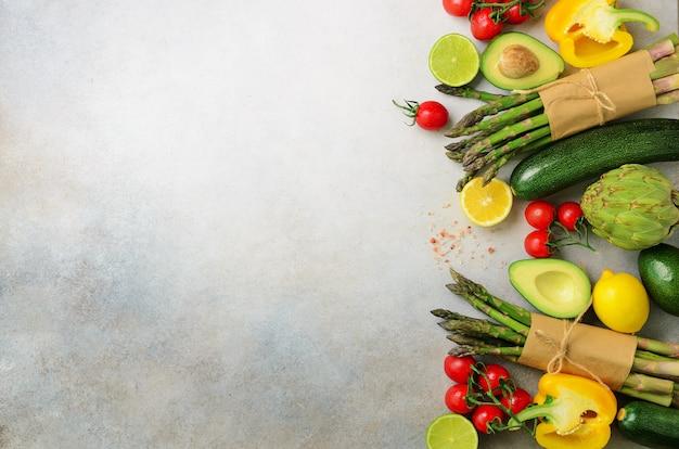 Różne organiczne warzywa - szparagi, pomidory wiśniowe, awokado, karczoch, pieprz, limonka, cytryna, sól na szarym tle.