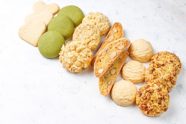 Różne orzechowe ciasteczka orzechowe, orzechowe, migdałowe i matcha na lekkim stole