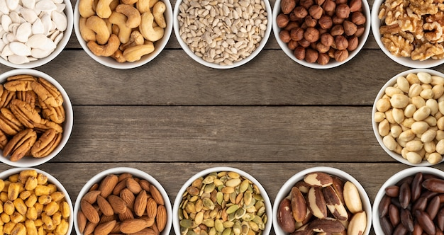Różne orzechy i nasiona w miskach na drewnianym stole z miejsca na kopię.