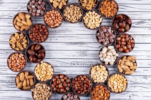 Różne orzechy i suszone owoce w mini miseczkach w kształcie cyklu z orzechami pekan, pistacjami, migdałami, orzeszkami ziemnymi, widok z góry