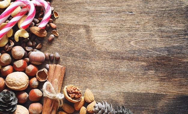 Różne orzechy na drewnianym stole. cedr, nerkowiec, orzech laskowy, orzechy włoskie i łyżka na stole. wiele orzechów jest w łupinach i chistchenyh na drewnianym tle
