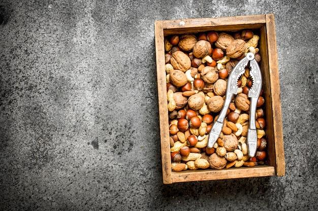 Różne orzechy w starym pudełku i dziadek do orzechów na rustykalnym tle