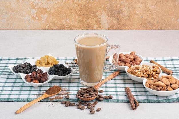 Różne orzechy z aromatyczną filiżanką kawy na obrusie. zdjęcie wysokiej jakości