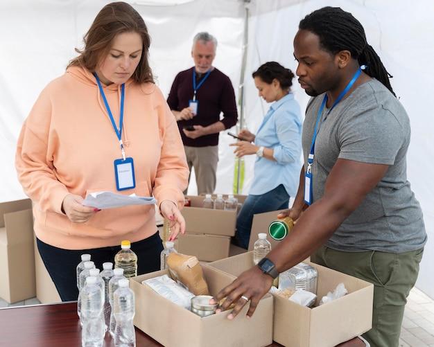 Różne osoby pracujące jako wolontariusze w banku żywności
