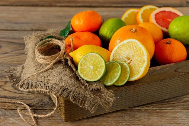Różne owoce cytrusowe w drewnianym pudełku. pomarańcza, mandarynka, grejpfrut, cytryna i limonka. na drewnianym tle.