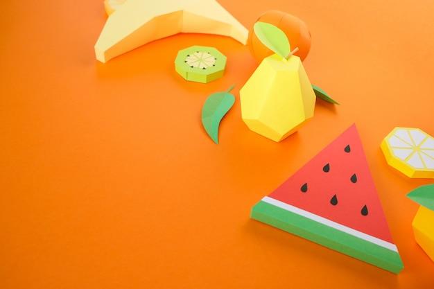 Różne owoce egzotyczne wykonane z papieru na pomarańczowym tle