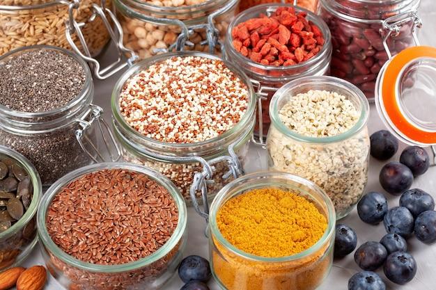 Różne owoce goji, komosa ryżowa, chia, nasiona konopi, nasiona lnu, ciecierzyca, owies, migdały, jagody, kurkuma, matcha i soczewica. wegańskie, wegetariańskie zdrowe jedzenie dieta koncepcja produktów ekologicznych