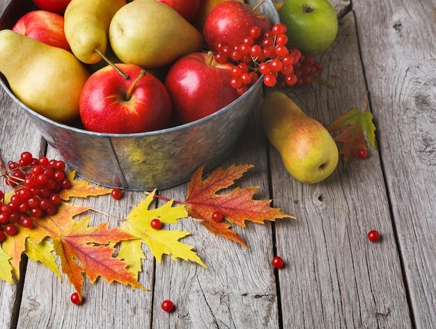 Różne owoce, jarzębina, jabłka, gruszki w starej metalowej misce i jesienne liście na zwietrzałym rustykalnym drewnie