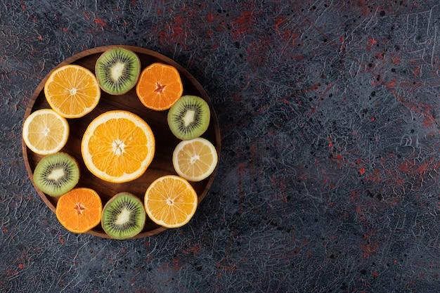 Różne owoce na drewnianym talerzu na marmurowej powierzchni