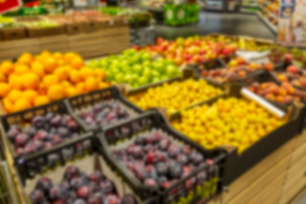 Różne owoce na ladzie w supermarkecie. zdjęcie jest rozmyte.