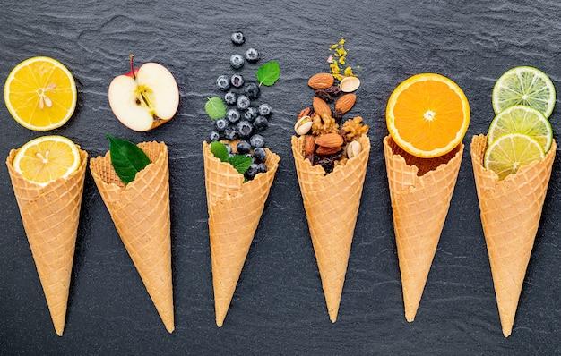 Różne owoce o smaku lodów w rożkach założonych na ciemnym kamiennym tle.