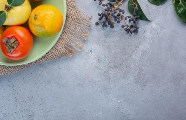 Różne owoce półmisek na kawałku tkaniny na tle marmuru.
