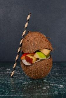 Różne owoce w kokosie pokrojonym na pół ze słomką na marmurowym stole