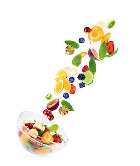 Różne owoce, w locie, lecą na talerz z owocami, na białym tle