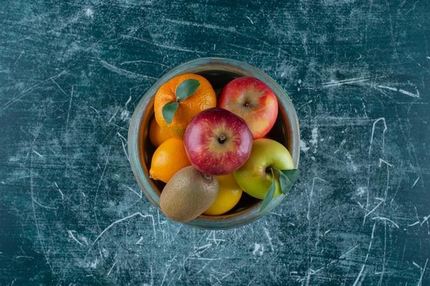 Różne owoce w misce na postumencie, na marmurowym stole.