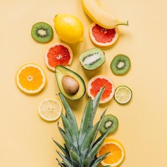 Różne owoce w pobliżu liści ananasa