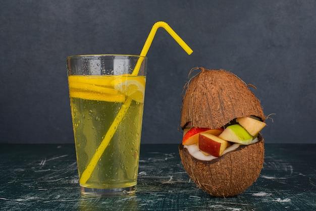 Różne owoce w pół kokosie i szklance soku na marmurowym stole.