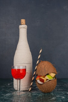 Różne owoce w połowie pokrojonego kokosa na marmurowym stole.