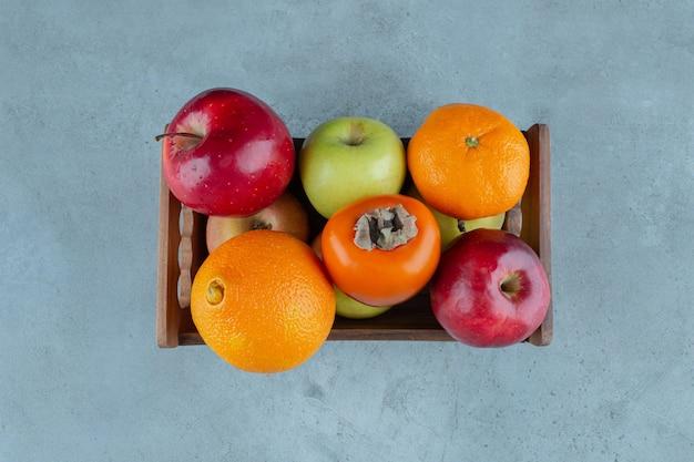 Różne owoce w pudełku, na marmurowym tle.