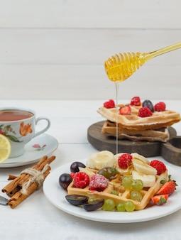 Różne owoce z goframi na talerzu z miodem, cynamonem, filiżanką herbaty