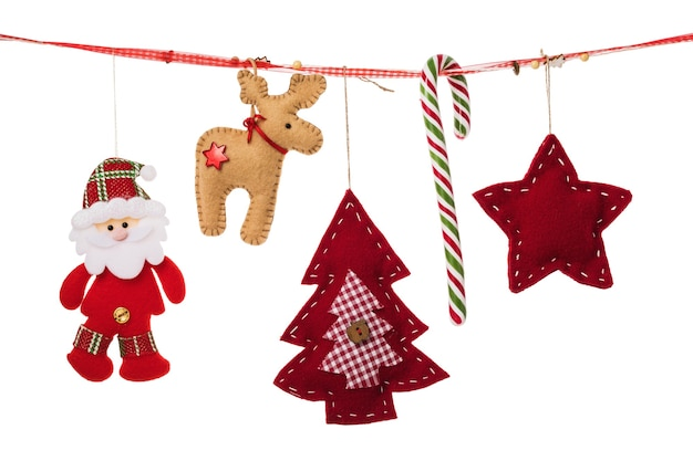 Różne ozdoby świąteczne wiszą na ozdobnej wstążce na białym tle
