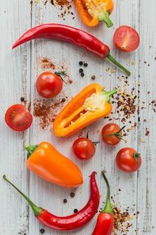 Różne papryki, pomidory koktajlowe i przyprawy na jasnej powierzchni drewnianej. przyprawy do żywności. domowe przyprawy do gotowania