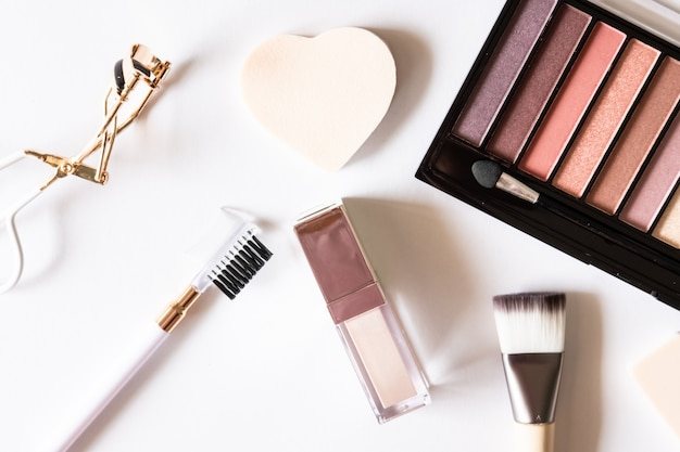 Różne pastelowe produkty kosmetyczne, paleta cieni do powiek, błyszczyk, grzebień, lokówka, pędzel i gąbki