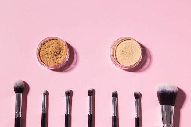 Różne pędzle do makijażu i puder mineralny do twarzy na różowym tle z kosmetykami do kopiowania z widokiem z góry