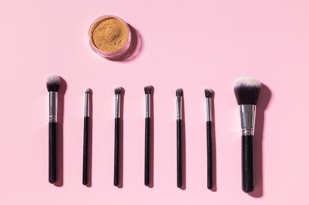 Różne pędzle do makijażu i puder mineralny do twarzy na różowym tle z miejscem na kopię, widok z góry. kosmetyki i koncepcja urody.