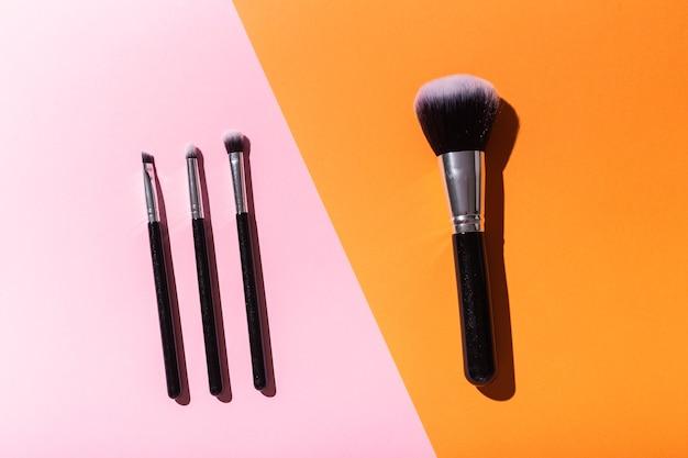 Różne pędzle do makijażu na różowym i pomarańczowym tle kosmetyki z widokiem z góry i koncepcja urody