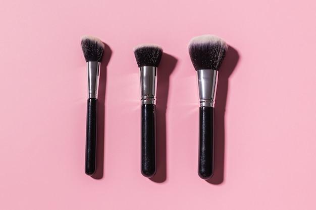 Różne pędzle do makijażu na różowym tle kosmetyki z widokiem z góry i koncepcja urody