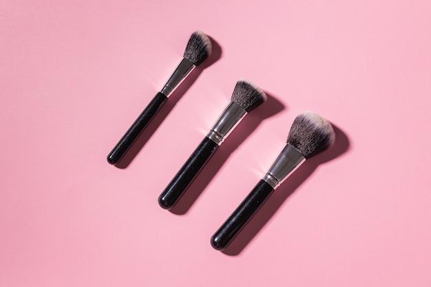 Różne pędzle do makijażu na różowym tle, widok z góry. kosmetyki i koncepcja urody.